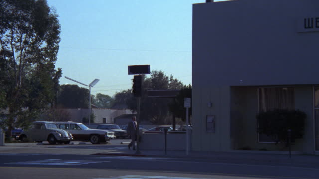 EST   ' WESTERN NATIONAL BANK ' MONEY  FINANCIAL INSTITUTION CAM FROM ACROSS STREET TRAFFIC MAN WALKS TOWARDS BANK FROM PARKING LOT USES KEYS TO OPEN FRONT DOOR