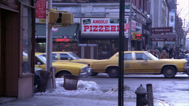wide angle of street in new york city during winter.  buses and taxi cabs. snow on ground. green sedan car pulls up to corner and man gets out of car and walks down sidewalk - anno 1983 video stock e b–roll