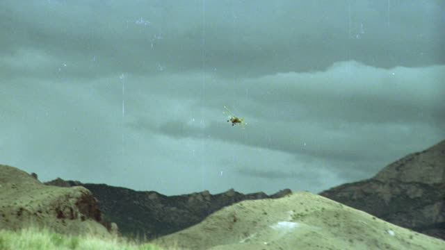 wide angle of yellow ford pick up truck driving up dirt road on side of mountain in desert. biplane flying up same path. propeller. dark clouds in bg. - ford truck stock videos and b-roll footage