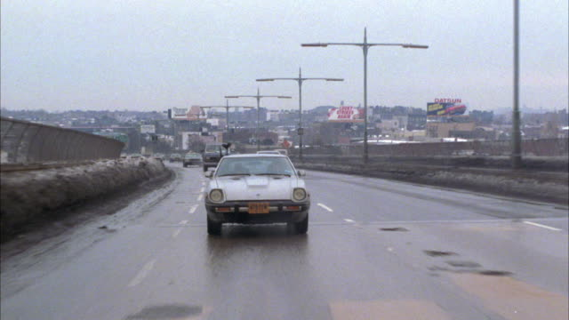 tracking shot of datsun driving on fdr drive in new york by tribeca bridge. from pov straight back. winter and overcast day. rainy street and see snow drifts on ground by expressway. - anno 1983 video stock e b–roll