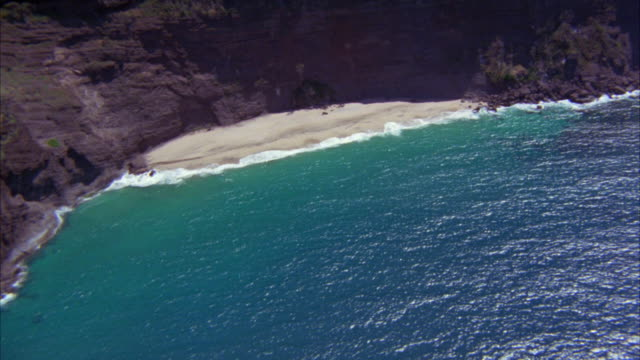 AERIAL OF SMALL BEACH OR COVE. ROCKY CLIFFS. OCEAN WAVES BREAKING ON THE SHORE. COASTLINE. COULD BE TROPICAL ISLAND.