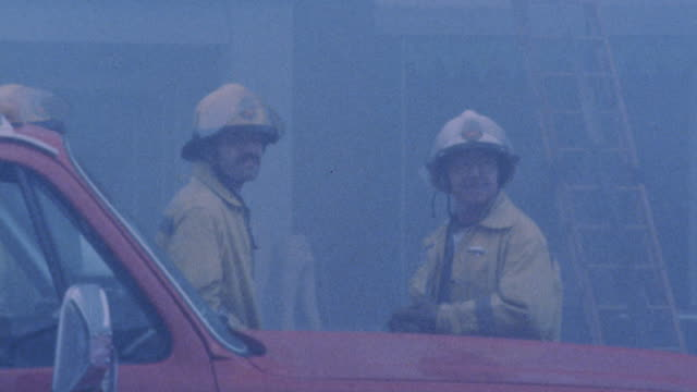 PULL BACK FROM TWO FIREFIGHTERS OR FIREMEN TALKING IN FRONT OF RED FIRE TRUCK TO SMOKE COMING FROM MULTI-STORY BUILDING. FIREMEN STANDING IN FRONT OF BUILDING, SPRAYING WATER FROM HOSE ONTO BUILDING.