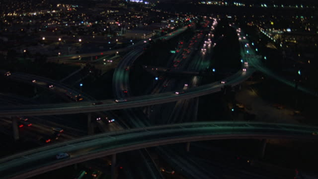 aerial over los angeles. headlights, taillights of cars, vehicles driving on freeways or highways, overpasses and freeway interchange visible. - 1982 stock videos & royalty-free footage