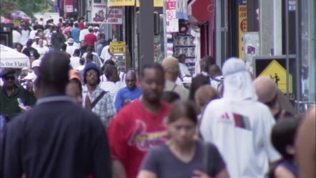 PAN L-R. EST. WS OVER TOP OF CROWD WALKING DOWN SIDEWALK. PAN R-L OVER HEADS OF PEOPLE WALKING.