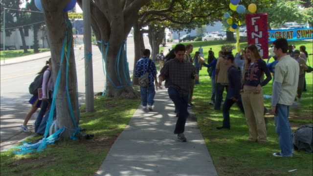 "ms. high school students walking and talking on sidewalk. grass on right, street on left. blue decoration on trees. sign reads ""finish."" blue and yellow balloons all around. - bean bag stock videos & royalty-free footage"