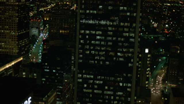 aerial over downtown los angeles. pass high rise and skyscraper office buildings. lights. cities. - 1987 bildbanksvideor och videomaterial från bakom kulisserna