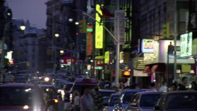 pan l-r over street of chinatown. cars and pedestrians in middle of street. restaurants and shops on street front. - chinatown stock videos & royalty-free footage