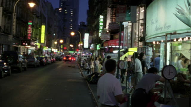 wide angle of storefronts in chinatown at night.  people buying and selling merchandise. pans right to left briefly to city street, and back to storefront - anno 2001 video stock e b–roll