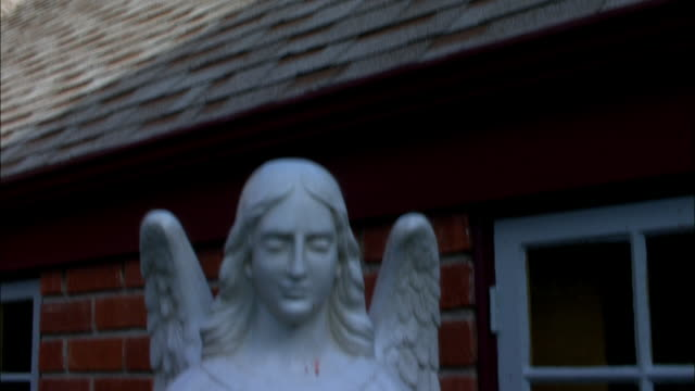 medium angle. white statue of angels with wings. pan up to  narrow, white church steeple behind brown tiled roof and cross on top of spire. blue sky in bg. - steeple stock videos & royalty-free footage