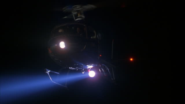 WIDE UP ANGLE TO BLACK POLICE HELICOPTER. SEE HELICOPTER WITH SEARCHLIGHT