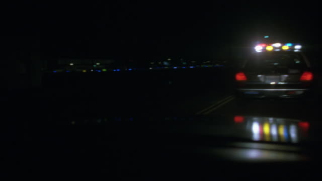 wide angle looking through windshield of police car. following another police car on small street beside airport. police car has lights flashing. cars begin to drive into airport and see helicopter above with searchlight on. - police force stock videos & royalty-free footage