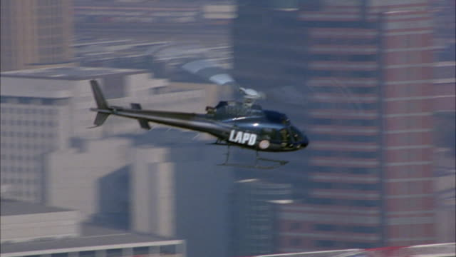 aerial over high rise buildings and skyscrapers. see black police helicopter flying in fg through buildings. shot pulls back, see wide angle of industrial area. - ヘリコプター点の映像素材/bロール