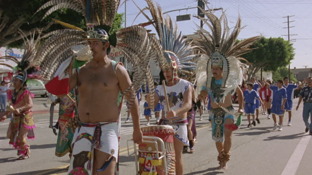 PAN LEFT TO RIGHT PARADE MARCHING DOWN CITY STREET. SEE NATIVE AMERICANS DRESSED IN NATIVE ATTIRE PLAYING DRUMS AND DANCING. CAMERA ZOOMS IN ON MAN PLAYING DRUMS, PANS DOWN TO DRUM THEN UP TO MAN WEARING NATIVE AMERICAN HEADDRESS.
