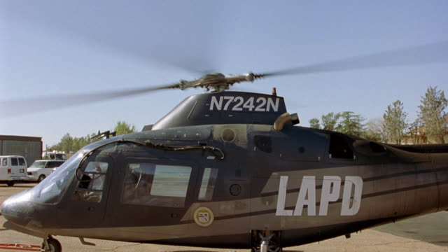 "zoom in. lapd helicopter on the ground with rotors spinning before take-off. zooms in on model number ""n7242n"" of helicopter below rotors. zooms in and out multiple times. - helicopter rotors stock videos and b-roll footage"