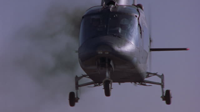 MEDIUM ANGLE. HELICOPTER HOVERING. BLACK SMOKE POURS OUT FROM BELOW ROTORS. HELICOPTER BECOMES UNSTABLE AND STARTS TO WOBBLE.