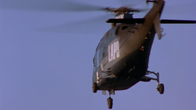 MEDIUM ANGLE. HELICOPTER HOVERING IN AIR. SMOKE COMES OUT OF TOP OF HELICOPTER. HELICOPTER STARTS TO SPIN IN CIRCLES WITH BLACK SMOKE COMING OUT OF TOP. PLUMMETS OUT OF SHOT AT BOTTOM.