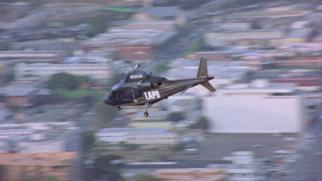 "tracking shot of police helicopter as it flies over industrial area. see ""lapd"" on side of helicopter. helicopter flies out of shot, shot pans down on apartment building. - helicopter stock videos & royalty-free footage"