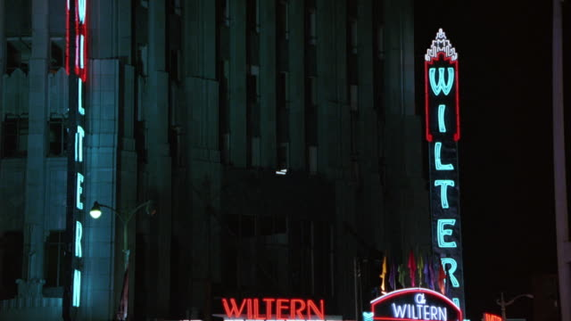 PAN UP TO VERTICAL SIGN THAT SAYS 'WILTERN'. PANS RIGHT AND DOWN TO CITY STREET. PANS LEFT, SEE POLICE CAR PARKED WITH LIGHTS FLASHING, AND L.A.F.D. AMBULANCE DRIVING ON STREET