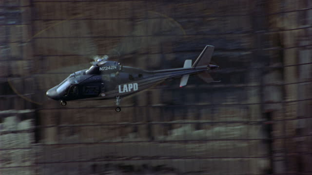 medium angle of lapd police helicopter flying by high rise buildings in downtown los angeles. shot tracks helicopter from right to left until helicopter leaves shot at end. - elicottero video stock e b–roll