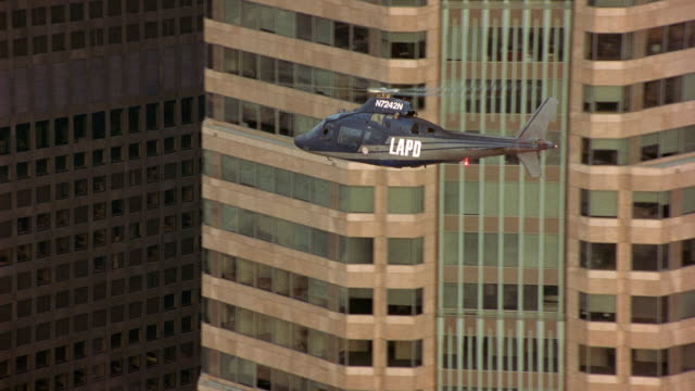 tracking shot of lapd police helicopter as it flies through high rise buildings in downtown los angeles. helicopter flies over industrial area. - helicopter rotors stock videos and b-roll footage