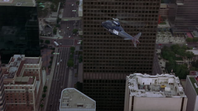 stockvideo's en b-roll-footage met air to air aerial of grey and blue lapd helicopter flying through high rise buildings of downtown los angeles. helicopter then rises over high rise buildings of city and circles around us bank tower. descends towards industrial area. - us bank tower