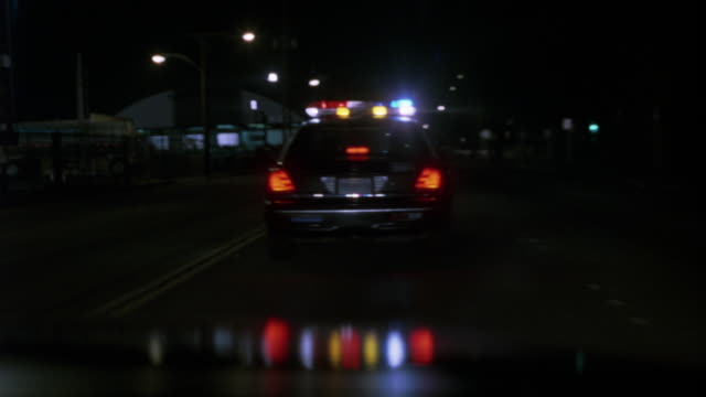 vídeos y material grabado en eventos de stock de medium angle. pov of passenger following police car. driving on highway or freeway at night. shot pans left and right back to police car. - coche de policía