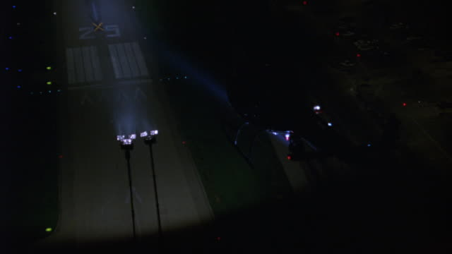 air to air aerial of lapd police helicopter flying over airport runway. see traffic on freeway at right. camera gets closer to helicopter, helicopter has spotlight on runway. - hubschrauber stock-videos und b-roll-filmmaterial