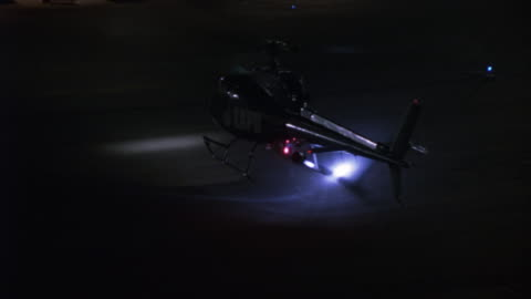 high angle down of lapd police helicopter landing on airport runway. see police cars with lights flashing lined up in background. camera circles to left, zooms in on helicopter. - helicopter stock videos & royalty-free footage