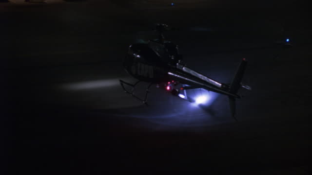 high angle down of lapd police helicopter landing on airport runway. see police cars with lights flashing lined up in background. camera circles to left, zooms in on helicopter. - helicopter landing stock videos & royalty-free footage