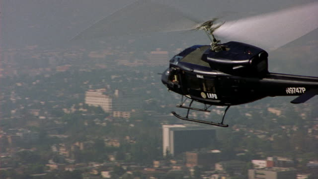 aerial following black police helicopter flying low past high rise buildings. smoggy. - helicopter stock videos & royalty-free footage