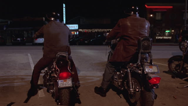 MEDIUM ANGLE FROM  BACK OF TWO MEN ON MOTORCYCLE CRUISERS. MEN TURN OUT OF PARKING LOT AND DRIVE OUT OF SHOT AT LEFT. SEE MARKET ACROSS THE STREET IN BACKGROUND AND PARKING METER IN FOREGROUND