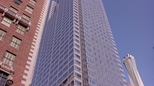 UP ANGLE OF SKYSCRAPER, COULD BE US BANK TOWER,  FROM GROUND. BRICK BUILDING ON THE LEFT AND THE LIBRARY TOWER IN THE BACKGROUND.