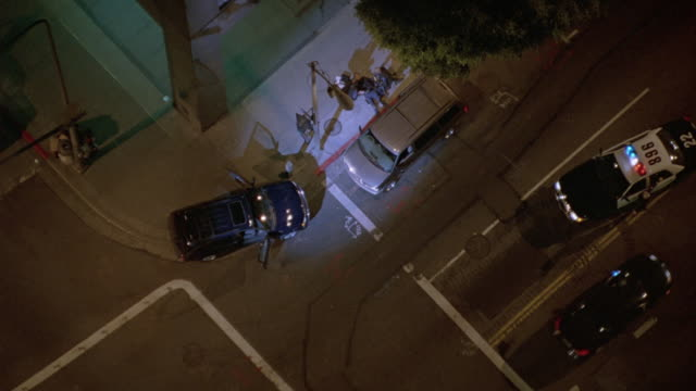 AERIAL BIRDSEYE POV WITH SPOTLIGHT ON POLICE SCENE. MAN LIES ON GROUND WITH SWAT MEMBERS STANDING BY. POLICE CARS PARKED NEARBY SCENE.