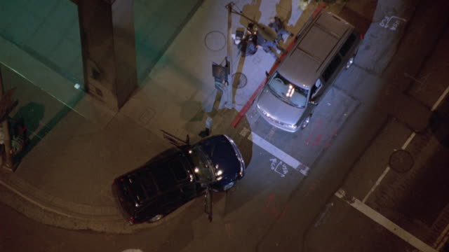 aerial birdseye pov with spotlight on police scene. see man lying on ground with swat members standing by. police cars parked nearby scene. - chevrolet stock videos & royalty-free footage