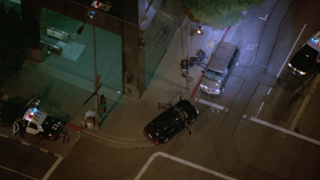 AERIAL BIRDSEYE POV WITH SPOTLIGHT ON POLICE SCENE. SEE MAN LYING ON GROUND WITH SWAT MEMBERS STANDING BY. POLICE CARS PARKED NEARBY SCENE.