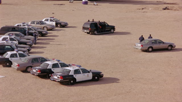 AERIAL OF ROW OF CARS, INCLUDING POLICE CARS, SUVS, AND CROWN VICTORIAS, PARKED BEHIND A BEIGE CROWN VICTORIA AT AN AIRFIELD. BLACK SUBURBAN WITH SWAT TEAM MEMBERS HANGING ON SIDE OF CAR DRIVES THROUGH AIRFIELD