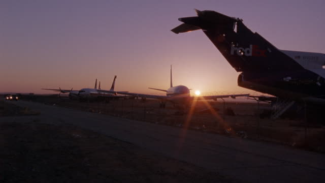 wide angle of commercial airplanes lined up on airfield. see sunset in background. pov from across street of airfield. black chevrolet suburban and white crown victoria drive toward camera. - airfield stock videos & royalty-free footage