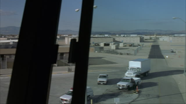 MEDIUM ANGLE LOOKING OUT FROM INSIDE GUARD TOWER. SHOT PANS RIGHT TO LEFT OF PRISON YARD. SEE PRISON BUILDINGS AND CHAIN LINK FENCES AROUND YARD. SEEMS TO BE SET IN DESERT. SEE MOUNTAINS IN BACKGROUND.