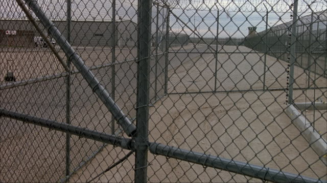 MEDIUM ANGLE OF PRISON YARD FROM OUTSIDE FENCE. PANS UP OVER BARBED WIRE AT TOP OF CHAIN LINK FENCE. SEE BUILDINGS SURROUNDING PRISON.