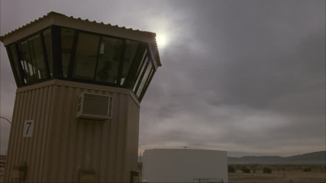 UP ANGLE OF GUARD TOWER. SET IN PRISON YARD THAT SEEMS TO BE IN DESERT. SEE TWO MEN IN GUARD TOWER.