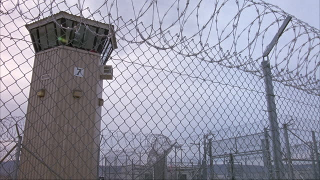 PAN UP OF  CHAIN LINK FENCE WITH BARBED WIRE ON TOP. CAMERA MOVES OVER FENCE, SEE GUARD TOWER TO LEFT, AND PRISON YARD. GROUP OF PEOPLE STANDING BY ENTRANCE OF PRISON.