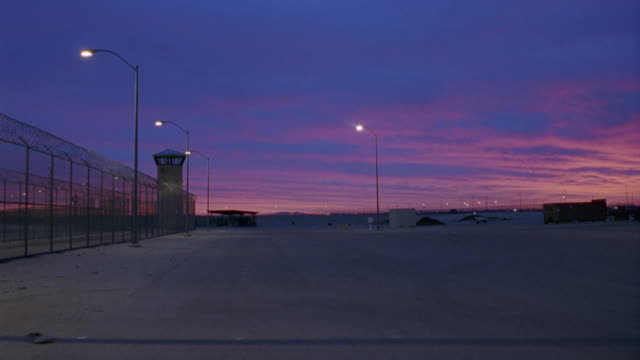 WIDE ANGLE SET IN PARKING LOT OF PRISON YARD. SEE GUARD TOWER IN BG. BEAUTIFUL BRIGHT ORANGE AND RED SUNRISE IN BG.