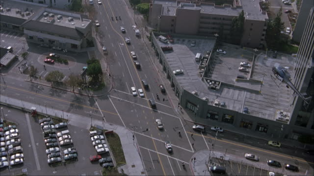 aerial birdseye pov of street in los angeles. looking down on motorcade moving through along street. lapd helicopter in bottom of shot. zooms in on motorcade and flies around to front of it. - motorcade stock videos & royalty-free footage