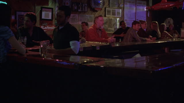 medium angle inside bar. see people sitting at bar and bartender serving drinks. - 2003 stock videos & royalty-free footage