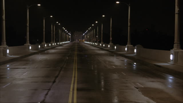 vídeos de stock, filmes e b-roll de wide angle. camera mounted on inside of car. car driving across bridge at night. ground is slightly damp with street lamps along bridge rail. car approaches barricades and a yellow truck blocking the bridge exit. - placa de processo