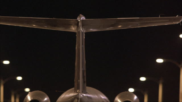 medium angle of tail of twin engine airplane moving down overpass or bridge. camera moves along side, blurred close angle of airplane. - airplane tail stock videos and b-roll footage