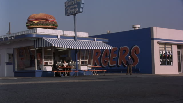 medium 3/4 side angle of storefront of fast food restaurant with big hamburger figure on roof. see two nuns eating and sitting on bench in front under canopy. - fast food restaurant stock videos & royalty-free footage