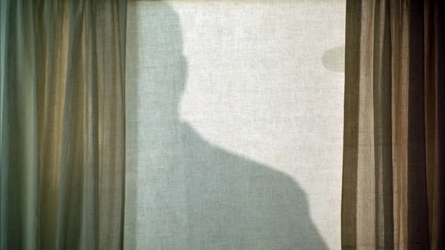 vídeos de stock e filmes b-roll de medium angle beige window shade, drapes or curtains on either side. see shadow of man wearing hat behind shade. - com sombra
