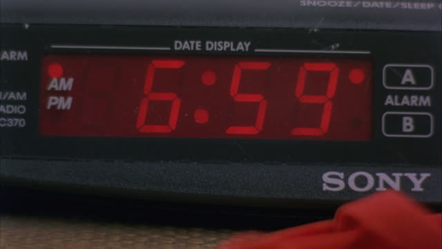 CLOSE ANGLE SONY CLOCK RADIO AND ALARM WITH RED LED NUMBERS. SEE CLOCK CHANGE FROM 6:59 AM TO 7:00 AM.
