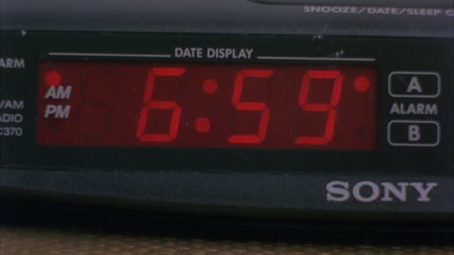 close angle sony clock radio and alarm with red led numbers. see clock change from 6:59 am to 7:00 am. - sony stock-videos und b-roll-filmmaterial